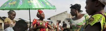 A Goma: le responsable  du marché de vente des posissons en provenances de Vitshumbi, Lac Edouard en plein Parc National des Virunga. Plusieurs femmes vendeuses des poisons de Goma achetent en gros dans ce marché. Sur cette proto, les vandeuses de possons sont autour du president du marché et attendant pour Payer avant de prendre les poisons qu'elles revendent dans les principaux marchés de la ville de Goma. Photo: Gautier Misonia.