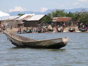 Les pêcheurs arrangent leurs filets pour les preparatifs de se rendre au lac pour pêcher, les autres sont de retour du lac decharge leurs poissons tandis que les collines observées au fin fond de la photo constituent les escarpements de KABASHA au PNVi. Ces escarpements constituent aussi les prolongement du Mont MITUMBA qui commence de LUBUMBASHI jusque dans la Province Orientale. Photo prise par Josué/COPEILE